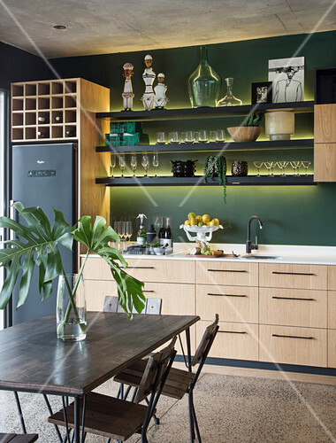Shelves with indirect lighting on green wall in kitchen-dining room