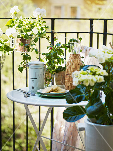 Round folding table on balcony surrounded by flowers