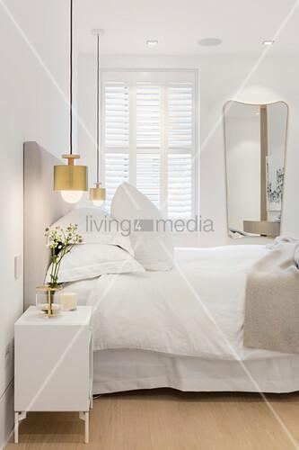 Goldene Pendelleuchten am Bett im Schlafzimmer in Weiß