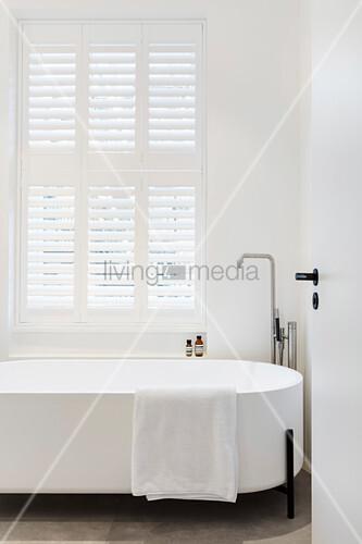 Modern, free-standing bathtub below window with shutters