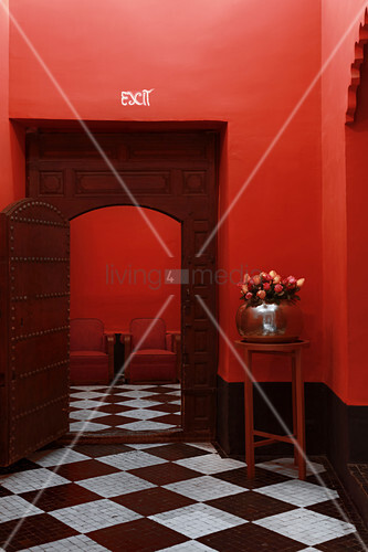 Old wooden door and surround in red wall in room with tiled chequered floor