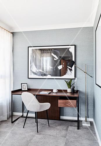 Schreibtisch aus dunklem Holz und heller Polsterstuhl im Arbeitszimmer mit grauer Tapete