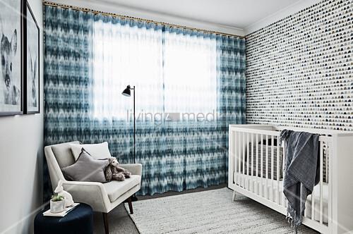 Gitterbett vor gemusterter Tapete, bodenlanger Vorhang und hellgrauer Polstersessel im Babyzimmer