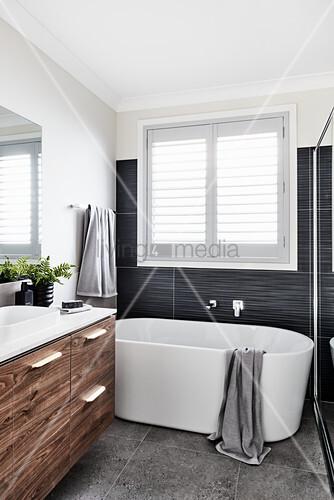 Free-standing bathtub below window and washstand with wooden doors in bathroom