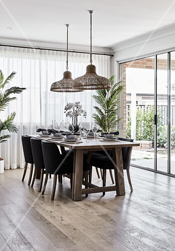 Set dining table next to terrace doors in open-plan interior