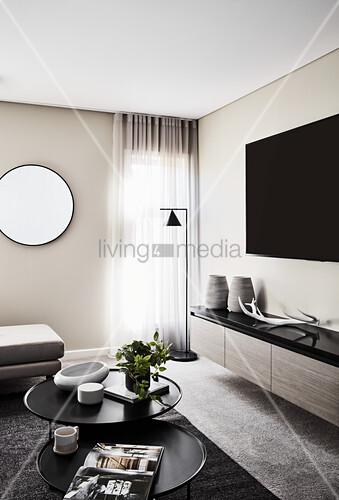 Fernseher über Lowboard und Couchtisch-Set in elegantem Wohnzimmer, runder Spiegel an der Wand