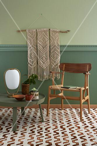 Makramee-Wandbehang, davor Stuhl und runder, niedriger Tisch auf gemustertem Teppichboden
