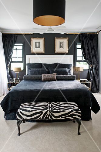 Double bed with black accessories and white headboard in bedroom with black wall and zebra-patterned bedroom bench