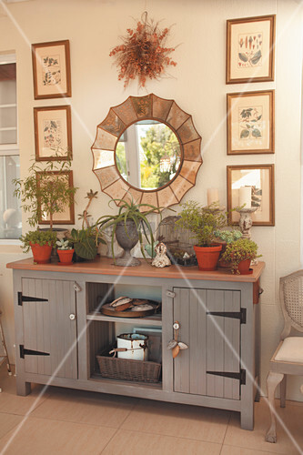 Gallery of pictures and mirror above grey, country-style sideboard