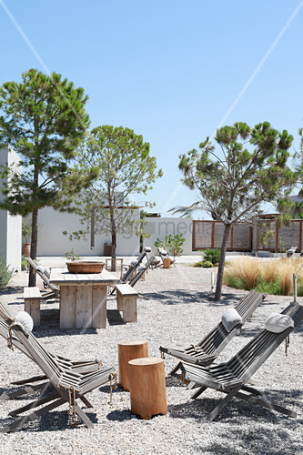 Deckchairs and wooden tables in gravel courtyard