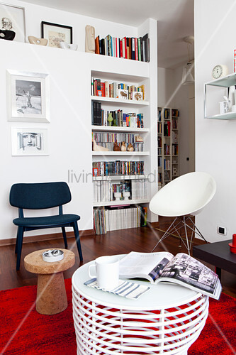 Interior with white walls, fitted shelves, various chairs and red rug as accent