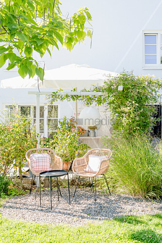 Two wicker chairs and side table on gravel terrace in late-summer garden