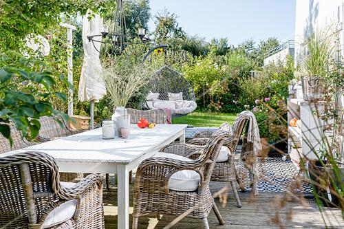 Terrasse im Herbst mit Terrassenmöbeln und Hängesessel