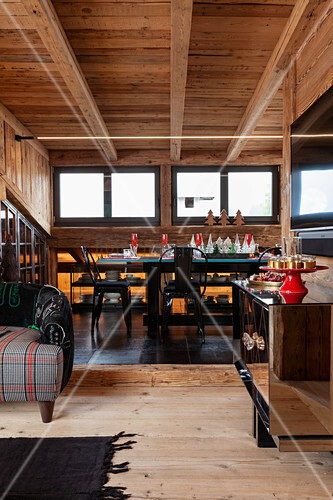 Open-plan interior of chalet with festively set table and black chairs