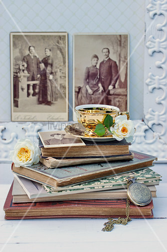 Rosenblüten an Kaffeetasse auf alten Büchern