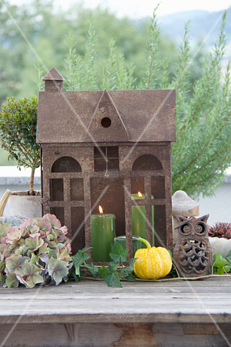 Autumnal arrangement with rusty, house-shaped lantern on terrace table