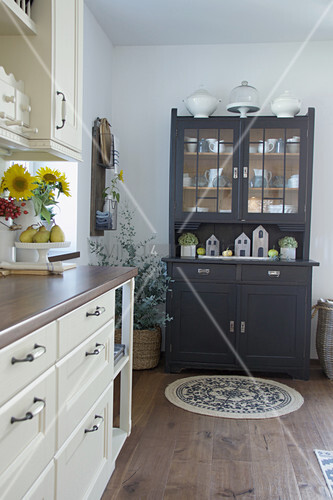 Off-white kitchen counter and grey dresser in country-house style in kitchen-dining room