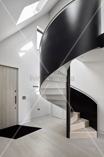 Black, modern spiral staircase in foyer of architect-designed house