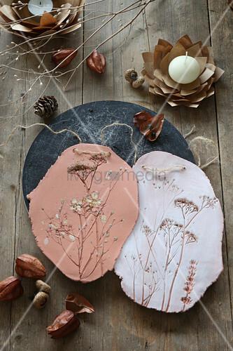 Tonbild mit Pflanzenabdrücken und Papierblüte als Kerzenhalter