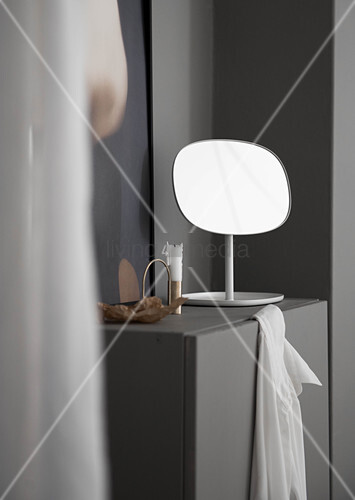 Mirror and candle on grey cabinet