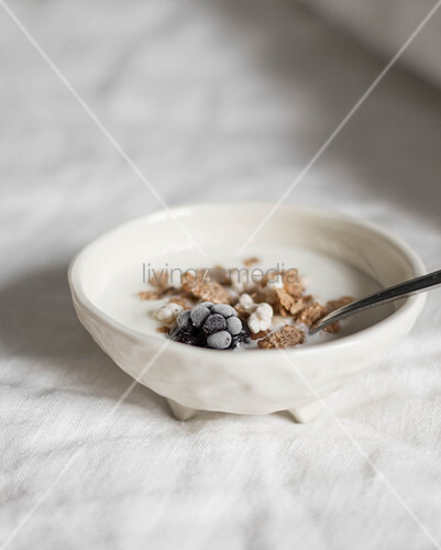 Bowl of cornflakes with yoghurt and frozen blackberries