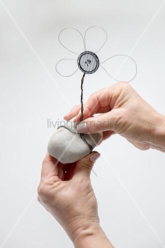 Drahtblume mit Knopf um einen Kieselstein gewickelt