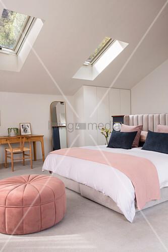 Sitzpouf im pastellfarbenen Schlafzimmer unter dem Dach