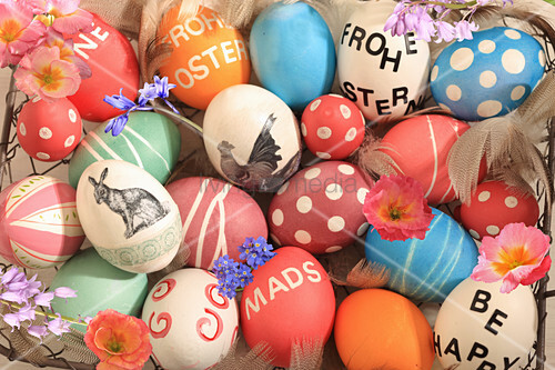 Easter eggs variously painted and decorated and spring flowers