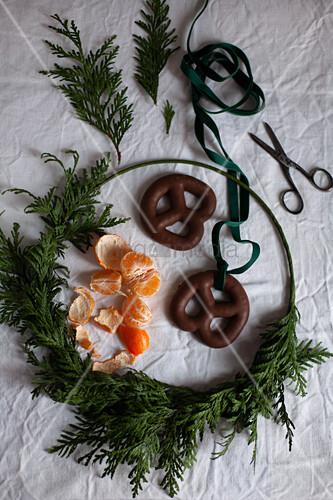 Weihnachtskranz, Mandarine, Schere und Lebkuchenbrezeln