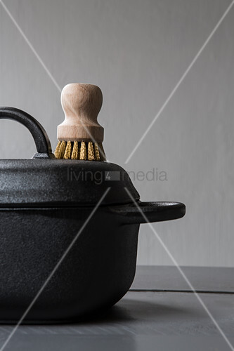 Black cooking pot with lid and wooden brush