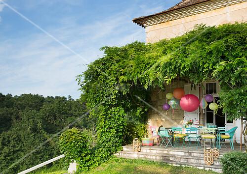 Bunt gestrichene Gartenstühle und Lampions auf der Terrasse