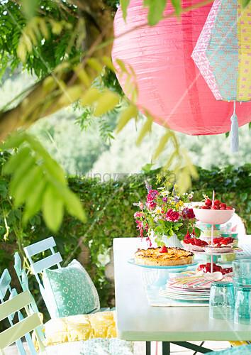 Lanterns hung above set garden table