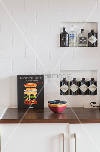 Bottles of spirits in niches in exposed brickwork of kitchen wall