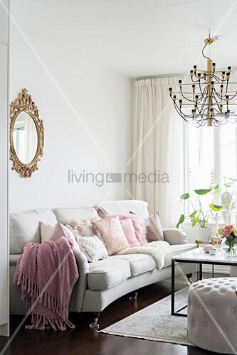 Weißes Polstersofa mit Kissen und Couchtisch in hellem Wohnzimmer