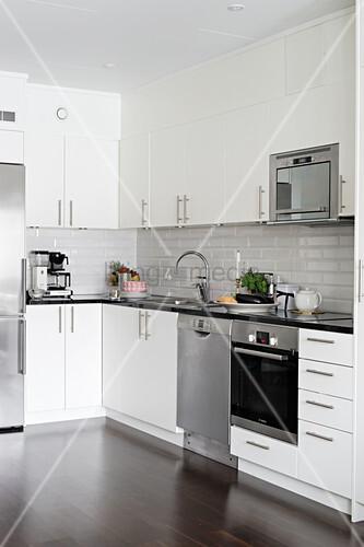 Stainless steel appliances in minimalist kitchen