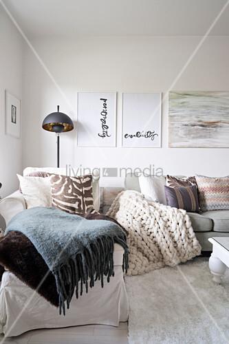 Verschiedene Plaids und Kissen auf Recamiere und Sofa unter Bildern ...