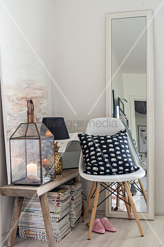 Chair and full-length mirror next to wooden bench and stacked magazines