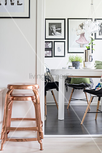 Two copper stools next to open doorway leading into dining room