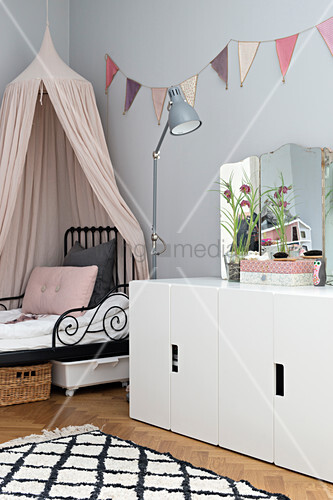 Bed with pink canopy and pastel bunting on wall in girl's bedroom