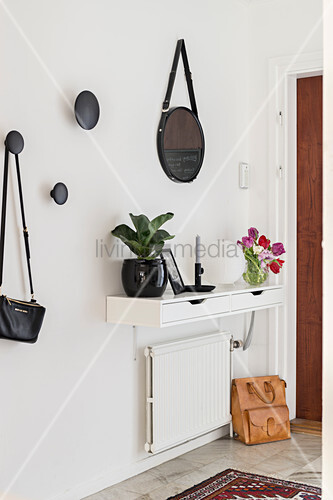 Narrow console in hallway with round mirror and coar hooks on wall