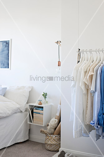 Suspended clothes rail in white bedroom