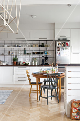 Set dining table with various chairs in large open-plan kitchen