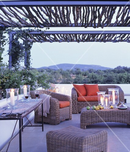 Wicker furniture and arrangement of candles on terrace at twilight
