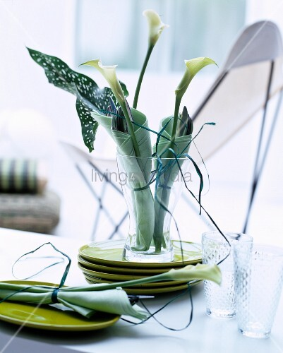 Table centrepiece in shades of green with calla lilies wrapped in napkins