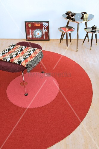 Stool on round rug next to three small retro tables