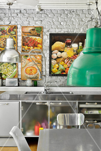 Stainless steel kitchen counter below framed pictures on white brick wall