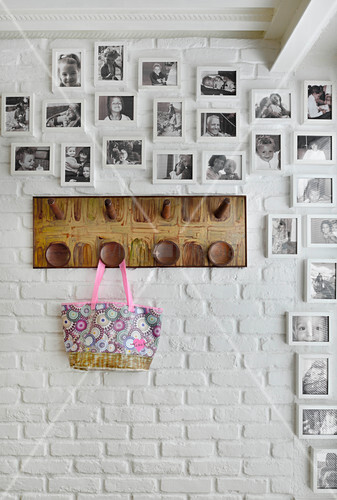 Framed black and white family photos and coat rack on white-painted brick wall