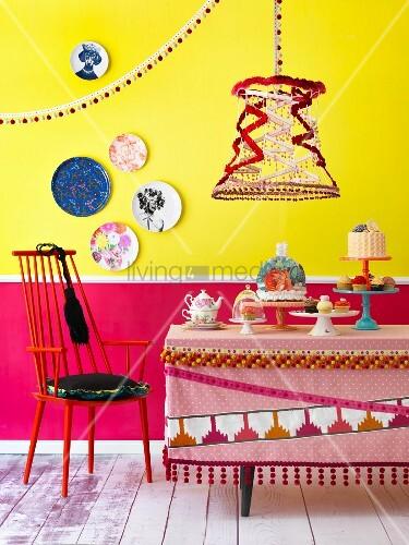 Bunte Tischszene vor zweifarbiger Wand