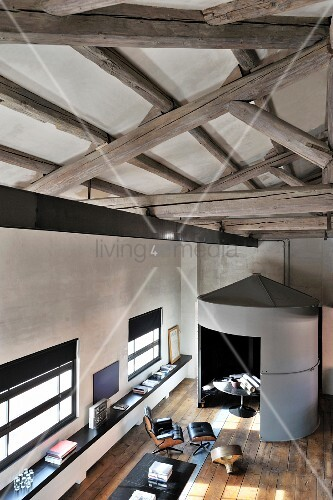 Rounded grey installation and restored wooden floor in modernised loft apartment