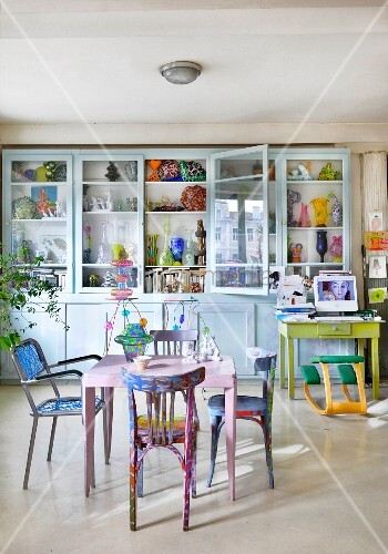 Table and colourful chairs in front of vases in glass-fronted cabinets
